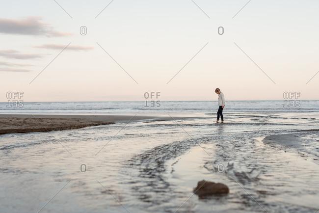 Blonde girl walking on beach in New Zealand