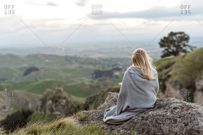 Girl wrapped in a blanket enjoying mountain view in New Zealand