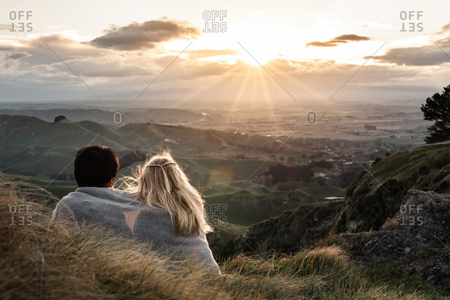 Two kids wrapped in a blanket enjoying mountain at sunset view in New Zealand