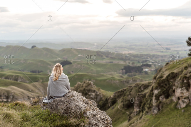 Blonde girl sitting on mountain wrapped in a blanket in New Zealand