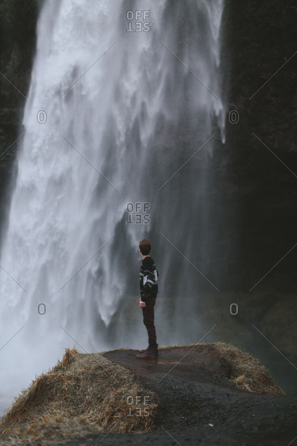 Boy looking at waterfall, Iceland