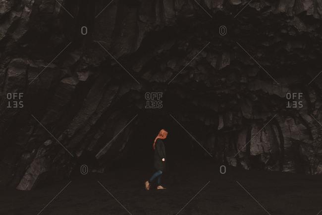 Girl walking on black sand beach, Iceland