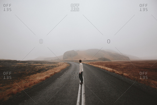 Boy standing in middle of road in foggy weather, Iceland