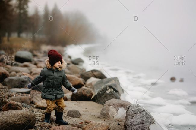 Boy throwing rocks in frozen lake
