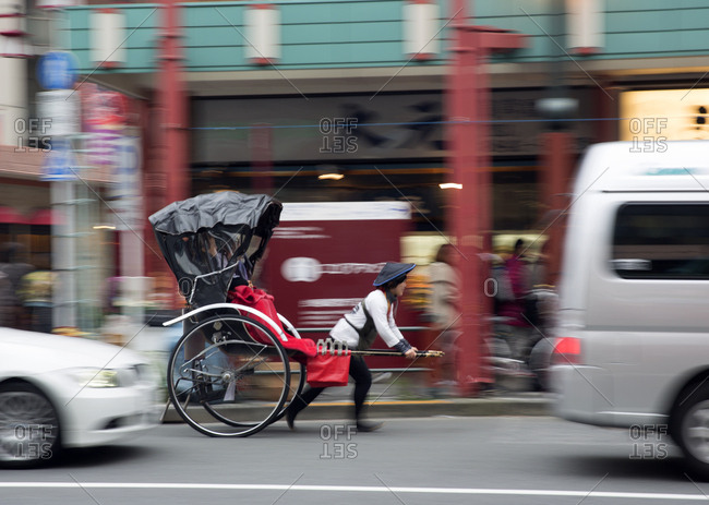 Tokyo, Japan - November 22, 2015: Asakusa shrine rickshaw in fast traffic
