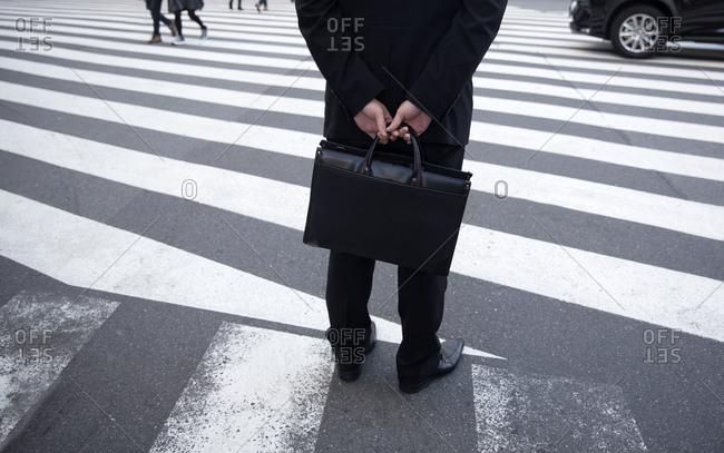 Businessman waiting at crosswalk