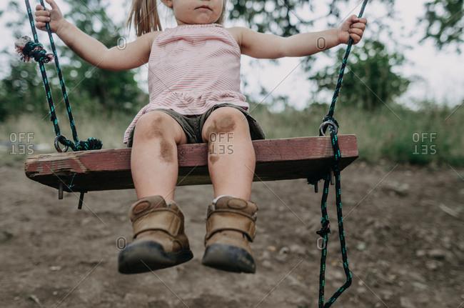 Muddy toddler swinging alone