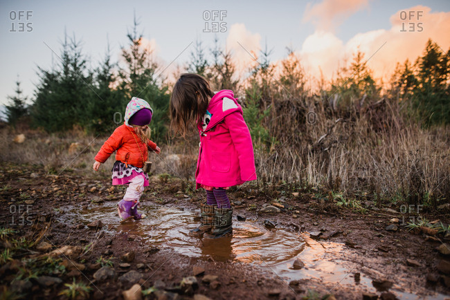 Sisters playing together in muddy meadow