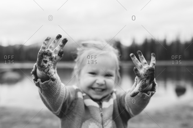Toddler shows off dirty hands outside