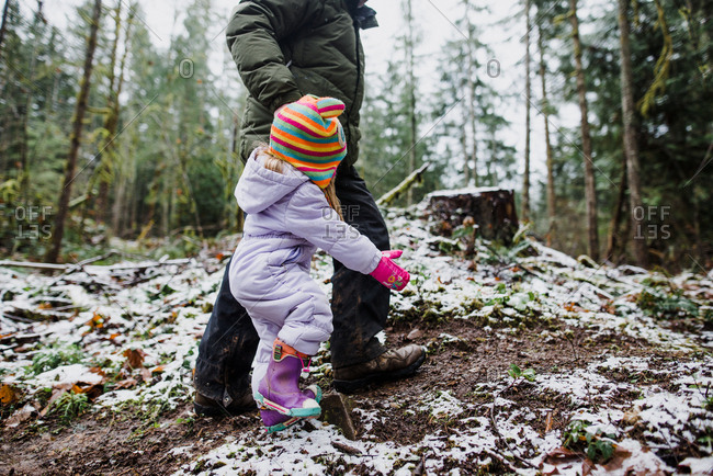 Older kid helps toddler walk through snowy mud