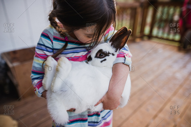 Girl clutching pet bunny rabbit close to chest