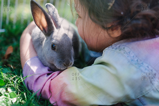 Girl hugging her rabbit friend outside