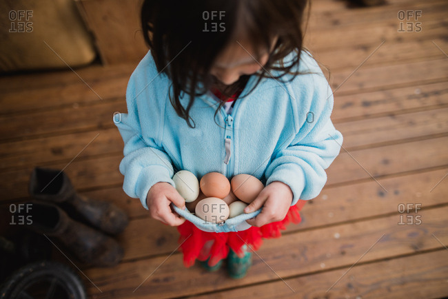 Girl carrying multiple fresh eggs in her sweater