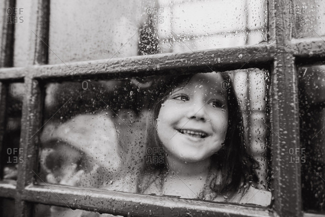Happy girl checks outside through rainy window