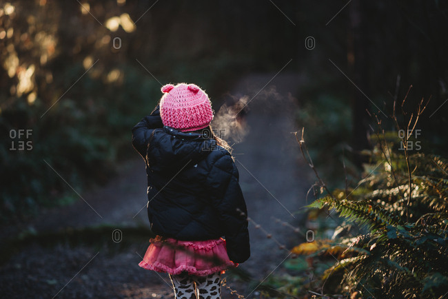 Little girl standing alone in forest path