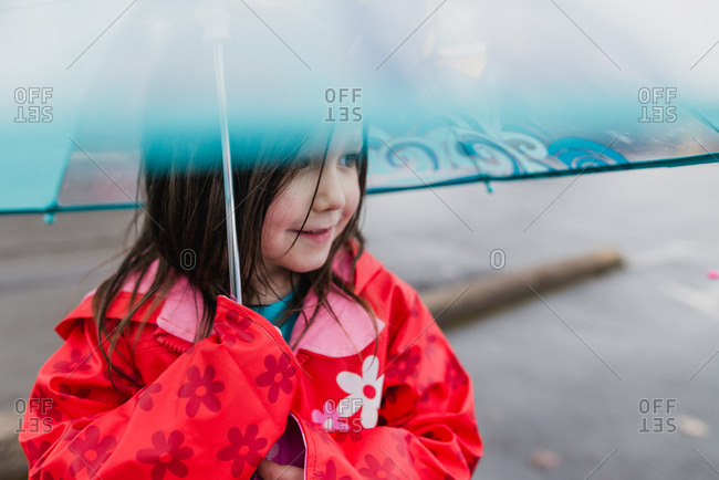 Girl keeping dry under umbrella
