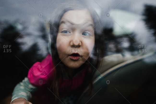 Little girl making silly faces against car window