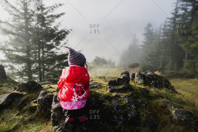 Lone girl sitting quietly by the mossy stones