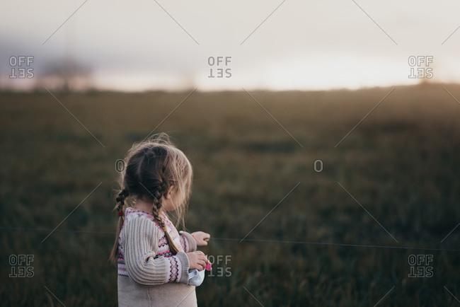 Small child watching sunset at wire fence line