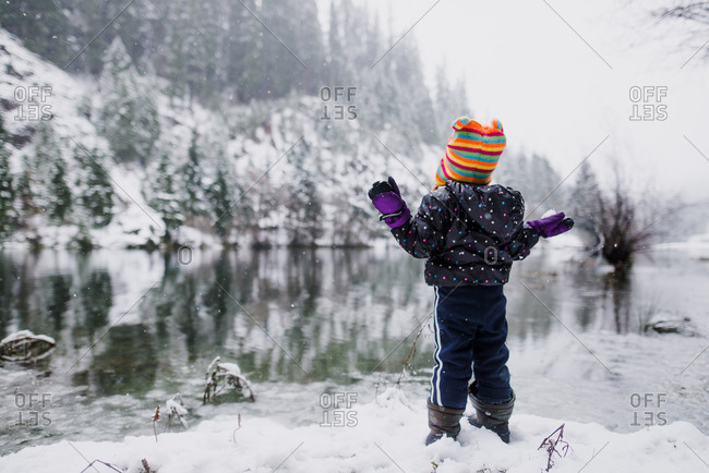 Child observing scenic winter lake