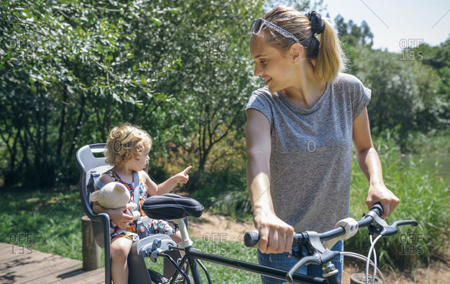 Mother taking a bike ride through the countryside with her daughter in a child seat