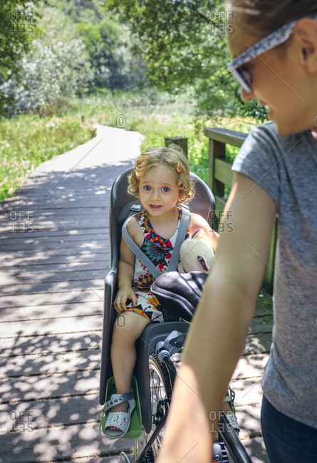 Little girl sitting on a child seat for bicycle with her mother