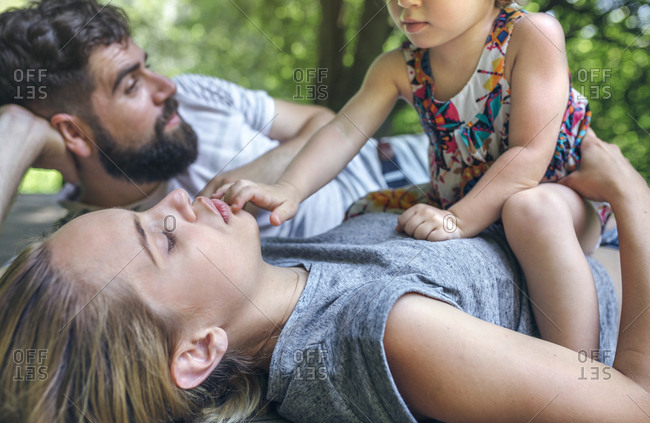 Little girl playing with her parents lying on a wooden walkway in the countryside