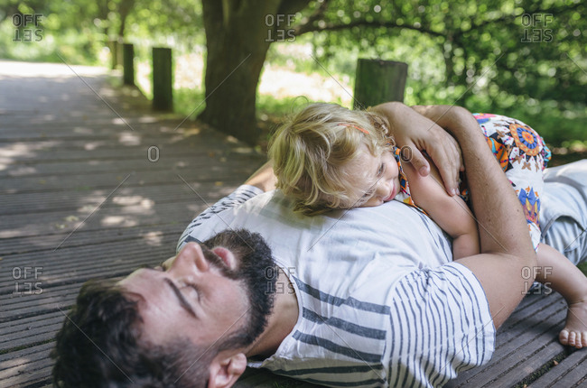 Little girl hugging her father lying on a wooden walkway in the countryside
