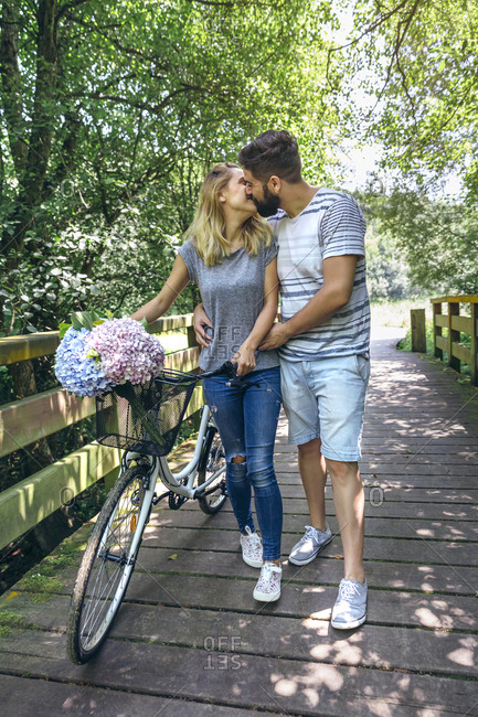 Couple with bicycle kissing on a wooden walkway in the countryside