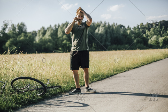 Young man on the phone- bicycle tour- accident