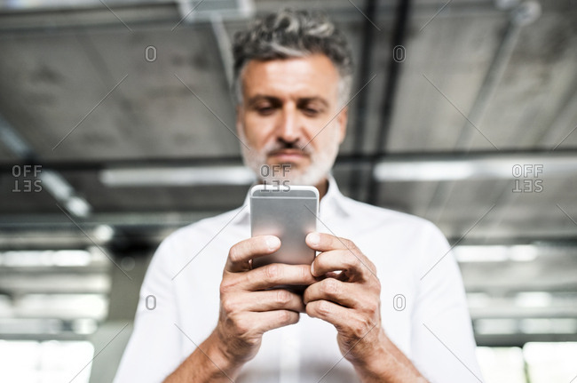 Low angle view of mature businessman holding cell phone