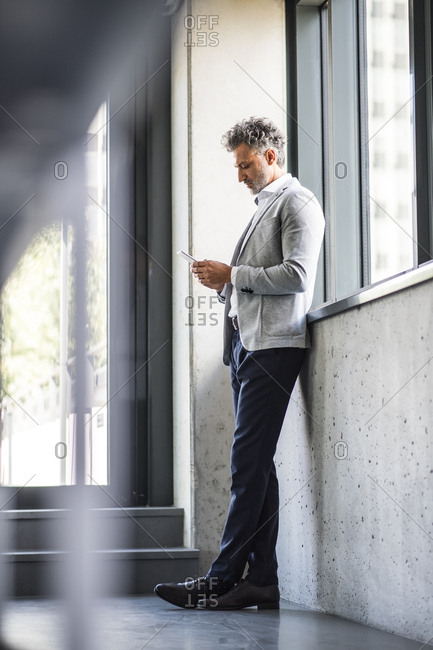 Mature businessman standing at the window holding cell phone
