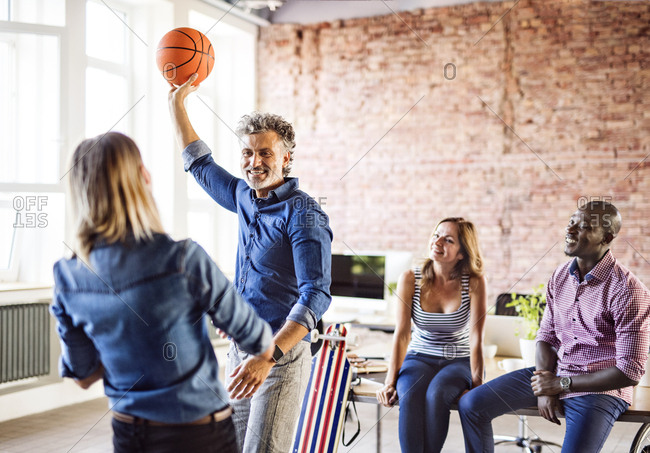 Colleagues playing basketball in office