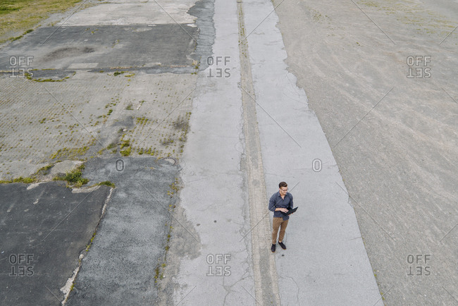 Young businessman using laptop in solitude- quadcopter view