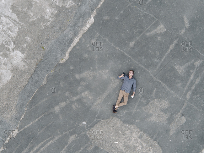 Young businessman with coffee to go lying on tarmac using mini tablet- quadcopter view