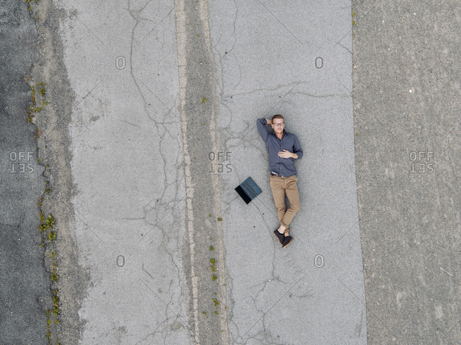 Young businessman with laptop relaxing in solitude- quadcopter view