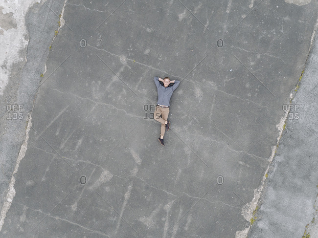 Young businessman relaxing on tarmac- quadcopter view quadcopter