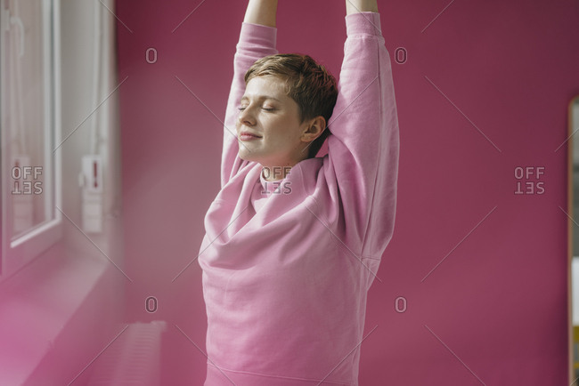 Woman in pink stretching at the window