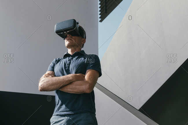 Mature man wearing VR glasses standing between walls of modern architecture