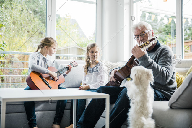 Two girls and grandfather on sofa playing guitar with dog watching