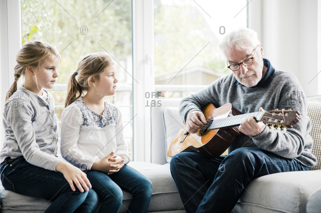 Two girls sitting on sofa listening to grandfather playing guitar