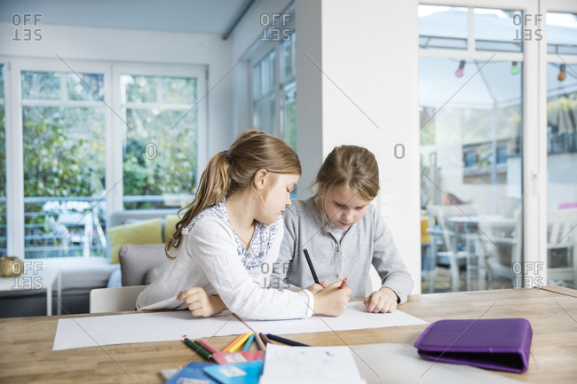 Two girls doing homework at table together