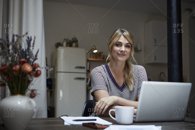 Portrait of smiling woman with laptop sitting at table in the kitchen