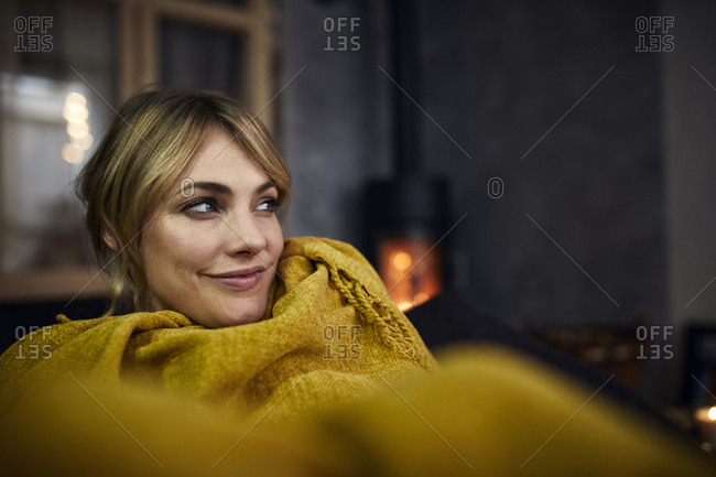 Portrait of smiling woman relaxing on couch at home in the evening