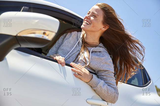 Young woman leaning out of window of a car