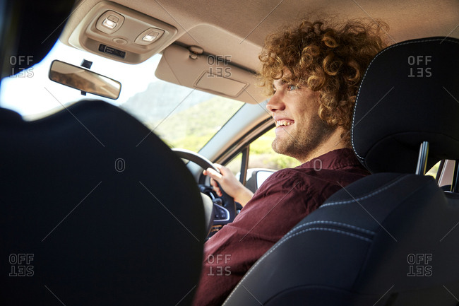 Young man driving car - Offset