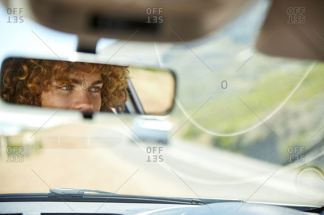 Young man driving car- rear view mirror- mirrored
