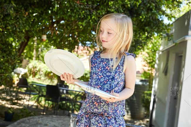 Blond girl holding plates in garden