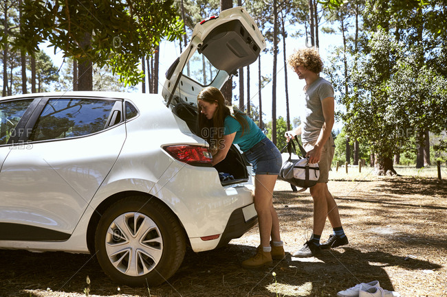 Young couple loading a car in forest