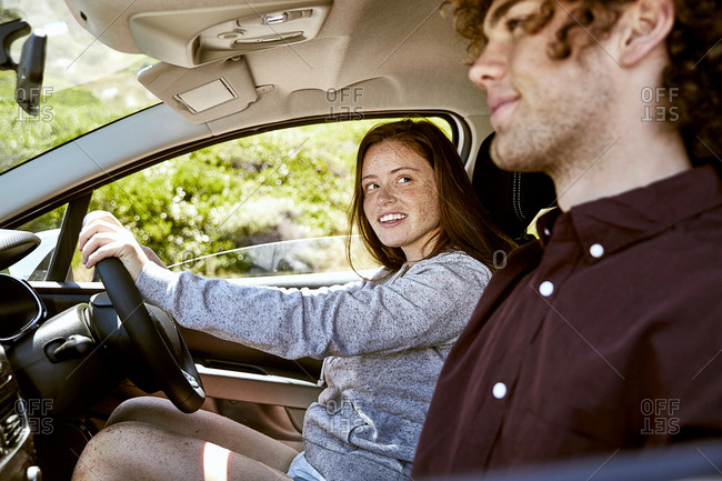 Smiling young woman driving car looking at her boyfriend